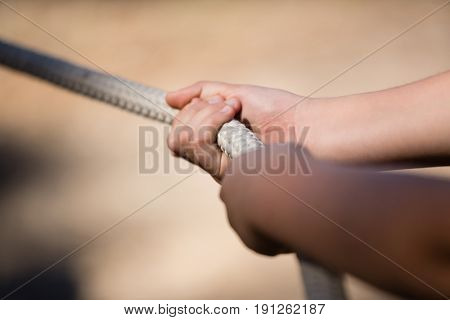 Hands of kid practicing tug of war during obstacle course in the boot camp