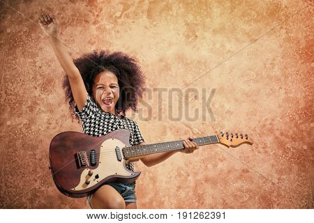 Afro-American little girl playing guitar on grunge background