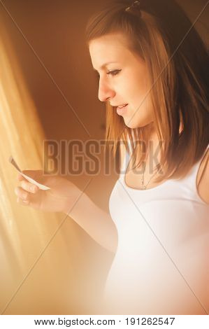 Young beautiful pregnant woman standing near window at home and holding ultrasound scan. Human pregnancy and expectation concept.