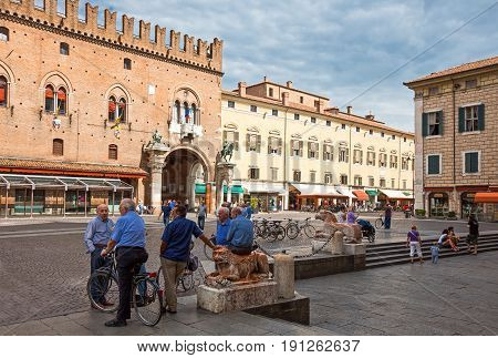 Ferrara Italy - July 21 2011: Older people in Duomo square with the Ducale palacein the background