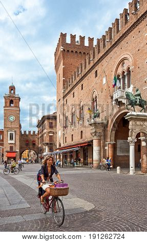 Ferrara Italy - July 21 2011: A young lady on a bicycle with the Ducale palace in the background