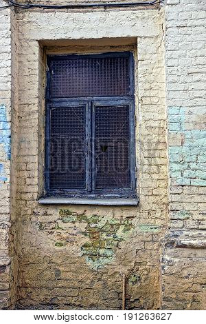 The old window with broken glass on the wall of a brick house