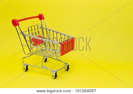 mini red color supermarket shopping cart on yellow background holiday sale and online shopping concept selective focus copy space