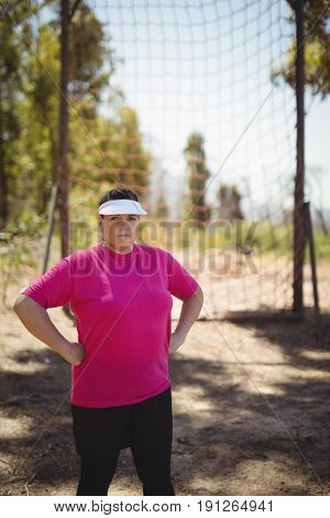 Portrait of woman standing with hands on hip in boot camp during obstacle course