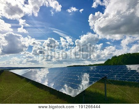 Clouds reflecting in solar photovoltaics panels field for renewable energy production with blue sky and clouds.