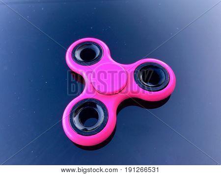purple fidget spinner stress relieving toy on dark background
