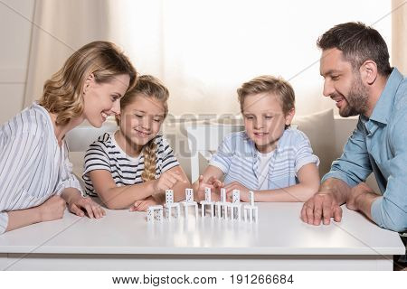 Smiling Family Sitting At Table And Playing With Domino Pieces
