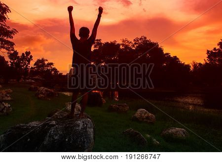 Silhouette of man meditating and yoga practicing with exercise at sunrise in the morning