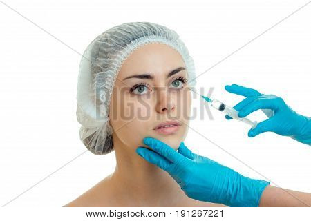 a young woman makes a prick in the face by a doctor isolated on white background poster