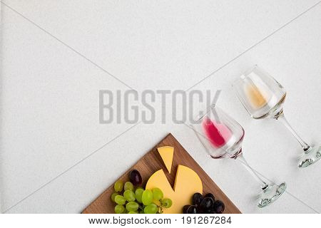 Two glasses of white and red wine, cheese and grapes. Top view with copy space