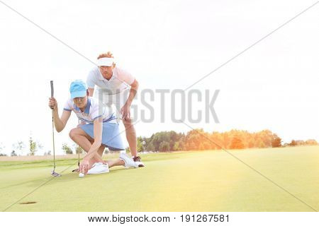 Man with woman aiming ball on golf course against sky