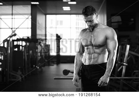 Strong muscular bodybuilder posing in gym, looking at his sixpack abdominal. Middle aged fitness model with naked torso. Black and white image.