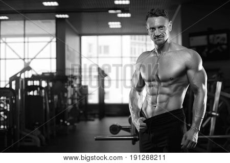 Sexy male fitness model showing perfect body, sixpack abdominal. Middle aged bodybuilder posing in gym. Black and white image.