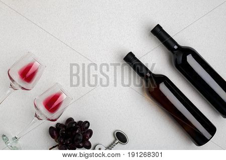 Two glasses of red wine and grapes. Two bottles of wine and a corkscrew. Top view with copy space