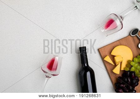 Two glasses of red wine, cheese and grapes. Bottle of wine and a corkscrew. Top view with copy space