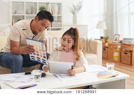 Portrait of young Asian couple choosing colors while planning new house design