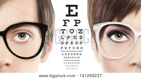 eyes and eyeglasses close up on visual test chart eyesight and eye examination concept in white background