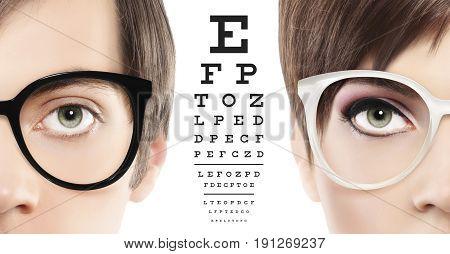 eyes and eyeglasses close up on visual test chart eyesight and eye examination concept in white background
