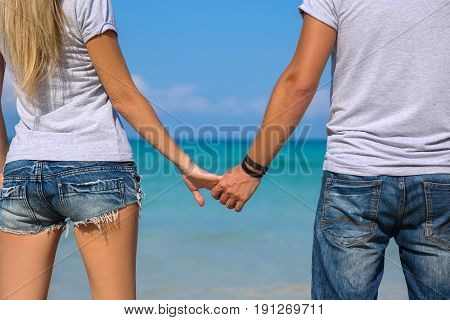 Happy couple walking hand in hand on white sand beach