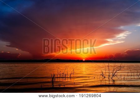 Beautiful sunset over a lake in Oklahoma with tree in foreground.