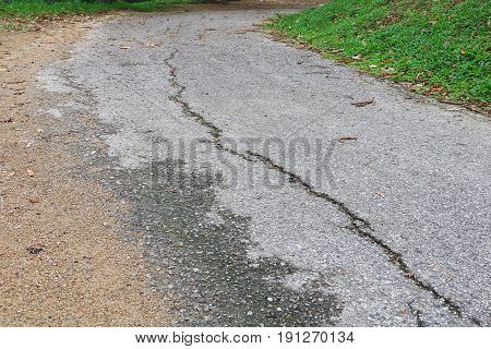 asphalt road cracked. street in public park