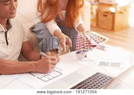 Closeup portrait of young family planning design of new house, choosing color scheme from swatches