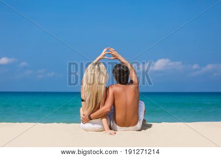 Romantic couple sitting on the beach and enjoying beautiful sea view side view spending time together summer vacation concept