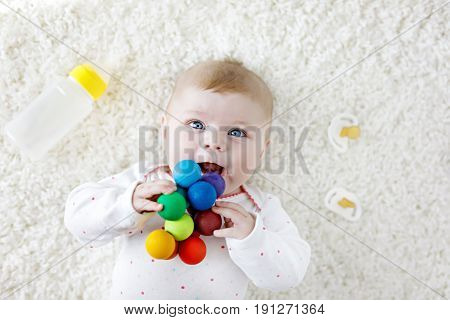 Cute adorable newborn baby playing with colorful wooden rattle toy, nursing milk bottle and dummy. New born child, little girl Family, new life, childhood, beginning concept