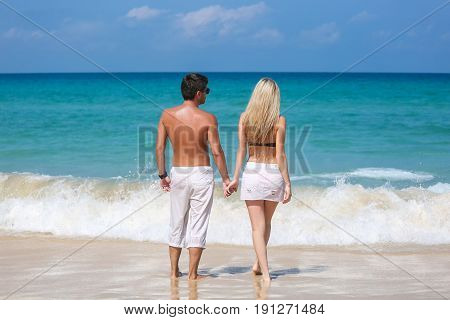 Romantic couple stand on the beach and enjoying beautiful sea view side view spending time together summer vacation concept