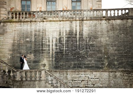A Look From Afar On A Bride Kissing A Groom Standing On The Stone Wall