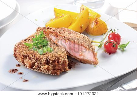 Fried luncheon meat sliced with potatoes on white plate