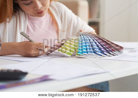 Closeup portrait of young Asian woman working with floor plans and color swatches choosing interior design for new house