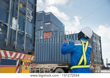 Foreman control loading Containers box from Cargo freight truck for logistics import export background.