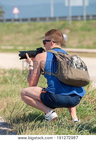 image of young man squatting with SLR camera