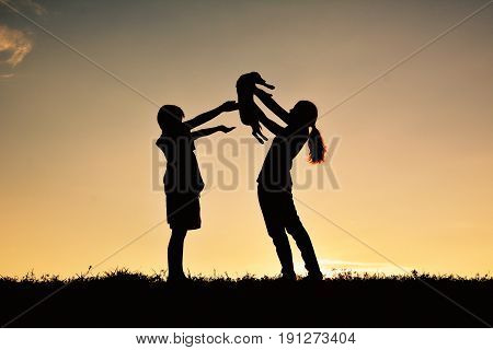 Silhouette mother and boy playing with little dog on the sky sunset color of vintage tone