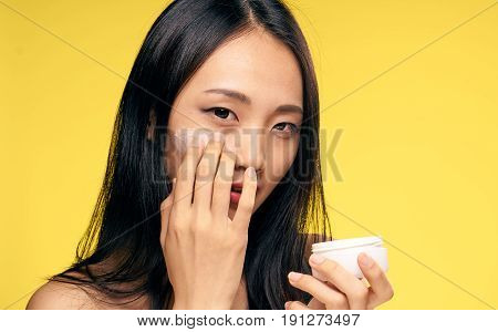 Woman is applying cream on face, woman is holding cream on yellow background.