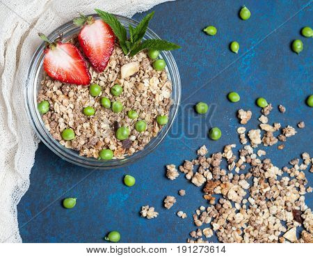 Sweet country breakfast: granola with strawberries and Green peas on vintage background. Top view, flat lay.
