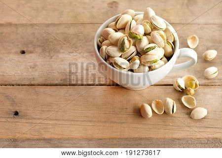 Pistachios are dried in a white cup on a wooden background.