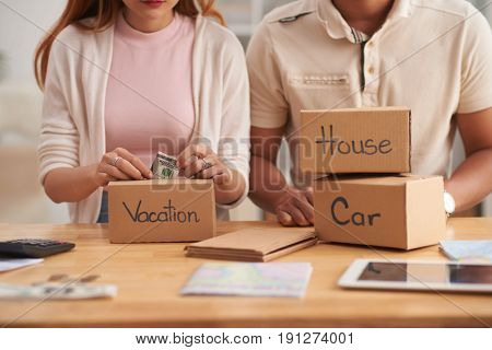 Closeup portrait of young family putting money to piggy banks, saving  for house, car and vacation