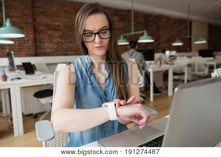 Female executive adjusting smart watch at desk in office