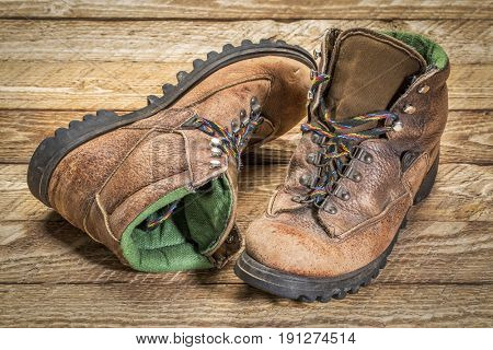 a pair of old, well-worn, hiking boots on weathered wood