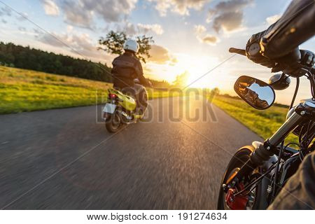 Motor bike riders driving towards beautiful sunset light on empty asphalt motorway. Photographed from driver perspective. Travel, freedom and transportation in outdoor nature