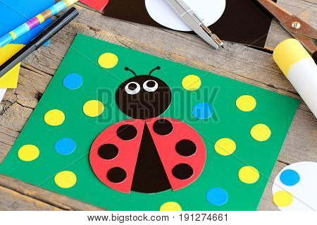 Ladybug paper collage. Ladybug card, stationery on a vintage wooden table. Children paper craft activity at home, in kindergarten or summer camp. Simple children crafts from paper circles. Closeup