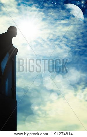 Man on balcony in backlight looking in a blue sky with sun moon stars clouds and bokeh