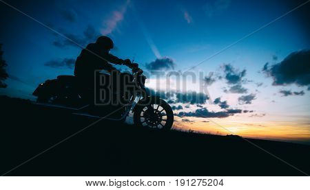 Dark motor biker silhouette riding high power motorbike in nature with beautiful sunset sky. Travel and transportation. Freedom of motorbike riding