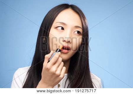 Woman is painting lipstick on a blue background portrait.