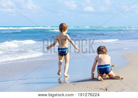 Two happy little kids boys running on the beach of ocean. Funny cute children, siblings, twins and best friends making vacations and enjoying summer on stormy sunny summer day. Miami, Florida.