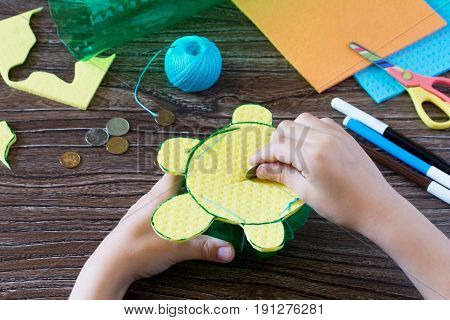 The Child Holds A Children's Hand-craft From A Plastic Bottle For Money Piggy Bank. Handmade. Projec