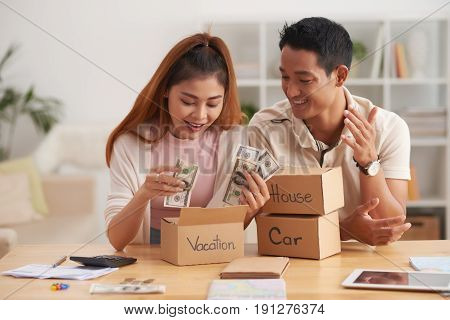 Portrait of young Asian couple putting money to piggy banks, saving  for house, car and vacation
