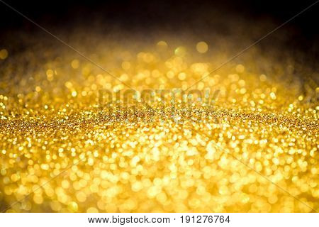 Sprinkle glitter gold dust on a black background abstract background texture